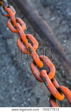 A red colored rusted chain with asphalt in bacground