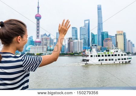 Woman waving goodbye at cruise ship leaving Shanghai city - Travel concept. Asian lady doing hello hand sign at ferry boat cruising on the Bund Huangpu river with Pudong skyline in the background.