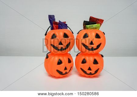 two stacks of Jack-O-Lantern with clolorful candies