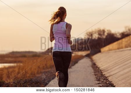 Female fitness woman training outside on a sunset. Sport lifestyle.