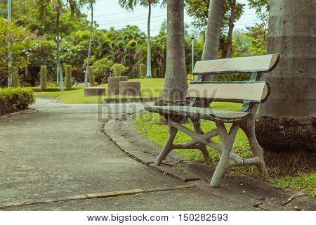 Wooden Park Bench Under  Trees. Vintage Tone .