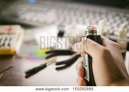 Man Prepares Coil Electronic Cigarette Smoking Tasty Vape Juice. Device For The Vaporization Service