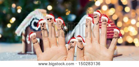 christmas, family, holidays, people and body parts concept - close up of two hands showing fingers with smiley faces in santa hats over gingerbread houses and lights background