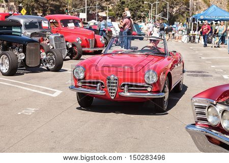 Laguna Beach, CA, USA - October 2, 2016: Man drives a red classic Alfa Romeo Milano car out of the Rotary Club of Laguna Beach 2016 Classic Car Show. Editorial use.