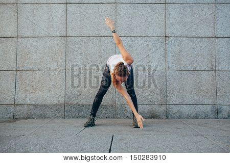 sporty woman doing stretching exercises incline outdoors