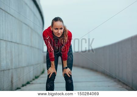 Young caucasian woman taking breath after jogging. Female athlete resting with hands on knees and looking away outdoors