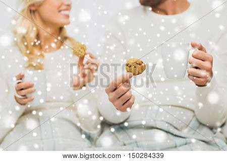 winter, love, food and sweets concept - close up of happy couple with oat cookies and tea cups at home