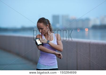sporty woman on river bank wearing sport armband looking faraway