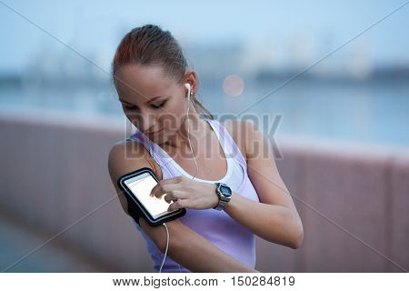 sporty woman on river bank wearing sport armband and touching her smartphone