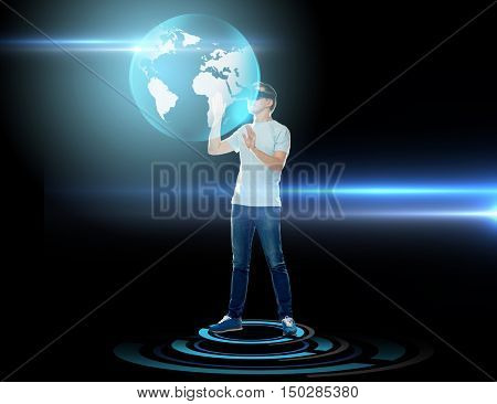 3d technology, augmented reality, entertainment, cyberspace and people concept - man with virtual reality headset or 3d glasses playing game and looking at earth globe hologram over black background