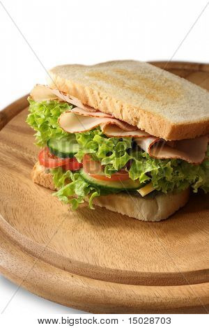 Delicious sandwich with layers of pickle, salad, cheese, tomatoes and turkey ham. Shallow depth of focus. Focus is on the front of the sandwich.