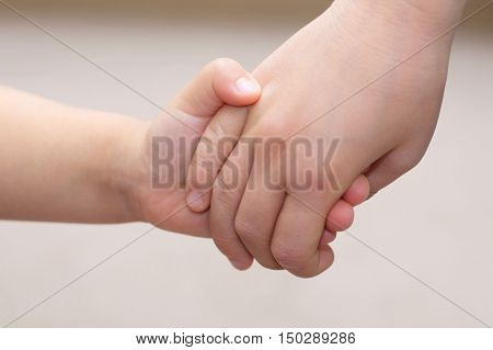 Kids hands together holding - childhood friendship concept