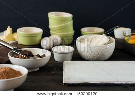 Ingredients for preparing a delicious chocolate dessert on a wooden table with a free place