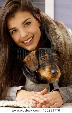 Closeup photo of attractive smiling woman hugging dog, looking at camera.