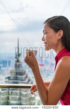 Asian woman enjoying afternoon high tea in luxury cafe or fancy restaurant with city view of Shanghai's landmark skyscrapers in Pudong, China. Chinese tourist lady drinking hot cup of coffee relaxing.