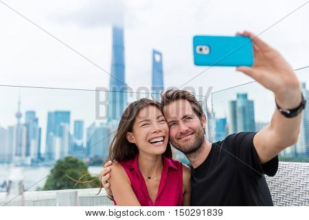 Chinese woman and Caucasian man taking smartphone selfie picture. Happy multiracial couple on travel holiday in Shanghai, China with phone on outdoor cafe terrace with view of the Bund and Pudong.