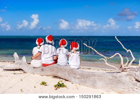 Back view of beautiful family wearing red Santa hats at tropical beach celebrating Christmas