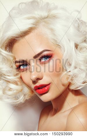Vintage style portrait of young beautiful sexy platinum blonde pin-up girl with curly hair and red lips