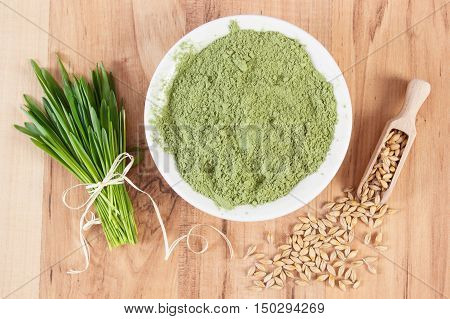 Heap Of Young Powder Barley, Barley Grass And Grain On Wooden Background