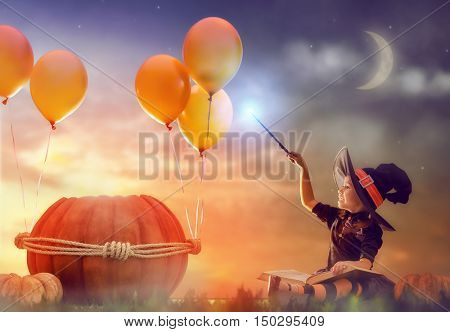 Happy Halloween! Cute cheerful little witch with a magic wand and book of spells. Beautiful child girl in witch costume sitting near the big pumpkin, conjuring and laughing.