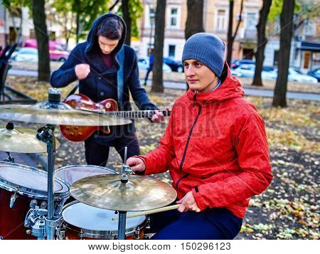 Music street male buskers playing percussions on autumn outdoor. Real man's music in autumn park