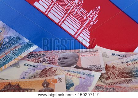 Cambodian riel notes with background of the Cambodian flag.
