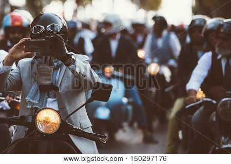 Crowd of elegant bikers riding motos. man taking photo using phone on foreground.