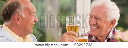 Closer shot of two elder men sitting face to face and drinking beer