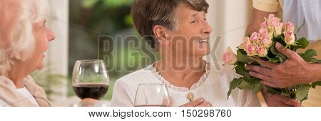 Delighted elder woman looking at the bunch of roses with a smile