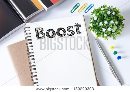 Text Boost on white paper book and pen, office supplies on white desk / business concept