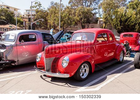Laguna Beach, CA, USA - October 2, 2016: Red 1940 Ford Deluxe Opera Coupe owned by Susan Reese and displayed at the Rotary Club of Laguna Beach 2016 Classic Car Show. Editorial use.