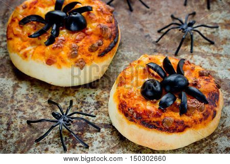 Halloween food background - funny mini pizza with olive spider decoration