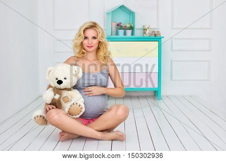 the pregnant woman sits and holds a teddy bear
