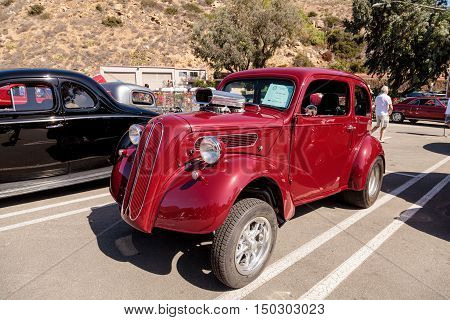 Laguna Beach, CA, USA - October 2, 2016: Red 1951 Ford Anglia Coupe owned by Bob Wells and displayed at the Rotary Club of Laguna Beach 2016 Classic Car Show. Editorial use.