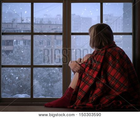 Girl sits on the window sill of the window and looks at the falling snow. The concept of home comfort season solitude