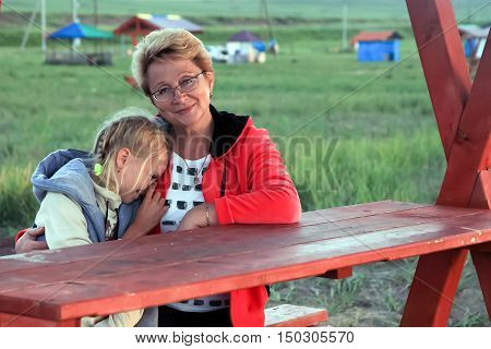 Grandmother hugging her grandson at a picnic table - the girl clung to her grandmother. They are together and happy.