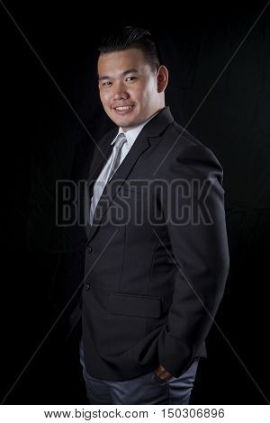 portrait smiling face happiness emotion of asian younger business man on black studio lighting