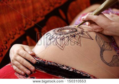 Tattoo master drawing henna tattoo on pregnant belly, closeup