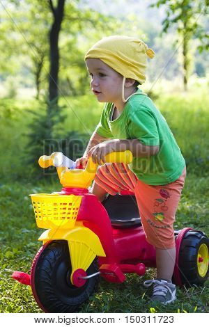 Child outside in garden with colorful toy tricycle