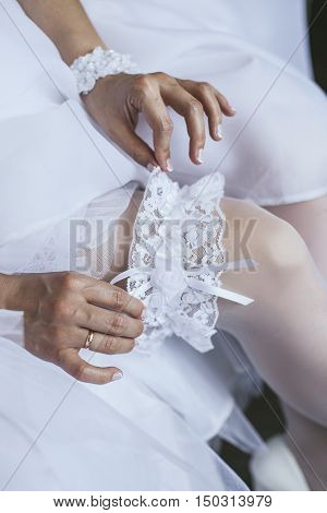 Bride is wearing a white lace garter on the wedding day closeup