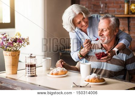 Spend time with pleasure. Smiling delighted elderly woman feeding her lovely husband with berries while enjoying the celebration and sitting in the kitchen.