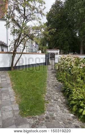 garden with porch and white painted wall of beguinage in flemish city of Bruges in belgium