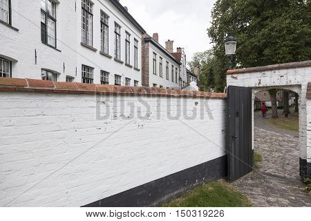 white painted wall of beguinage in flemish city of Bruges in belgium