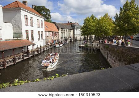 Bruges, Belgium 28 august 2016: tourist boat in bruges canal near antique bridge on sunny summer day in august