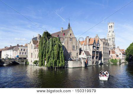 Maarssen, Netherlands, 30 september 2016: old houses and tourist boat in canal in centre of medieval Brugge in Belgium with blue sky in summer