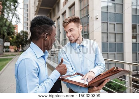 African American businessman and Caucasian businessman smiling and talking. OK gesture. partners came to an agreement