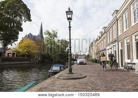 Maarssen, Netherlands, 30 september 2016: couple on bicycle passes houses along river Vecht in the dutch village of Maarssen in the netherlands