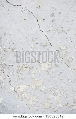 vertical part of old wheathered white stucco full of cracks on outside wall