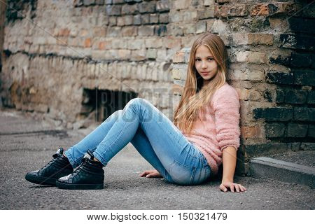 photo of beautiful young girl posing on the street