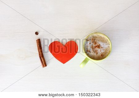 flat layout with heart symbol and cup of frothy cappuccino with cinnamon top view / I love coffee